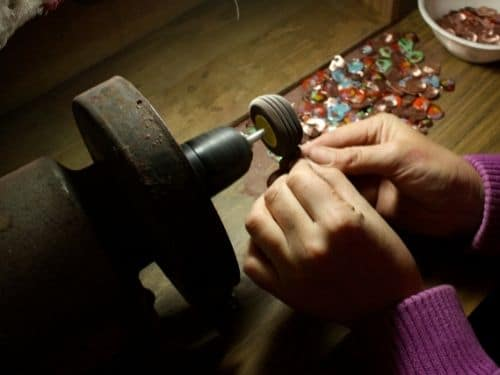After open firing, each piece of jewelry  has to be painstakingly cleaned on a grinder.